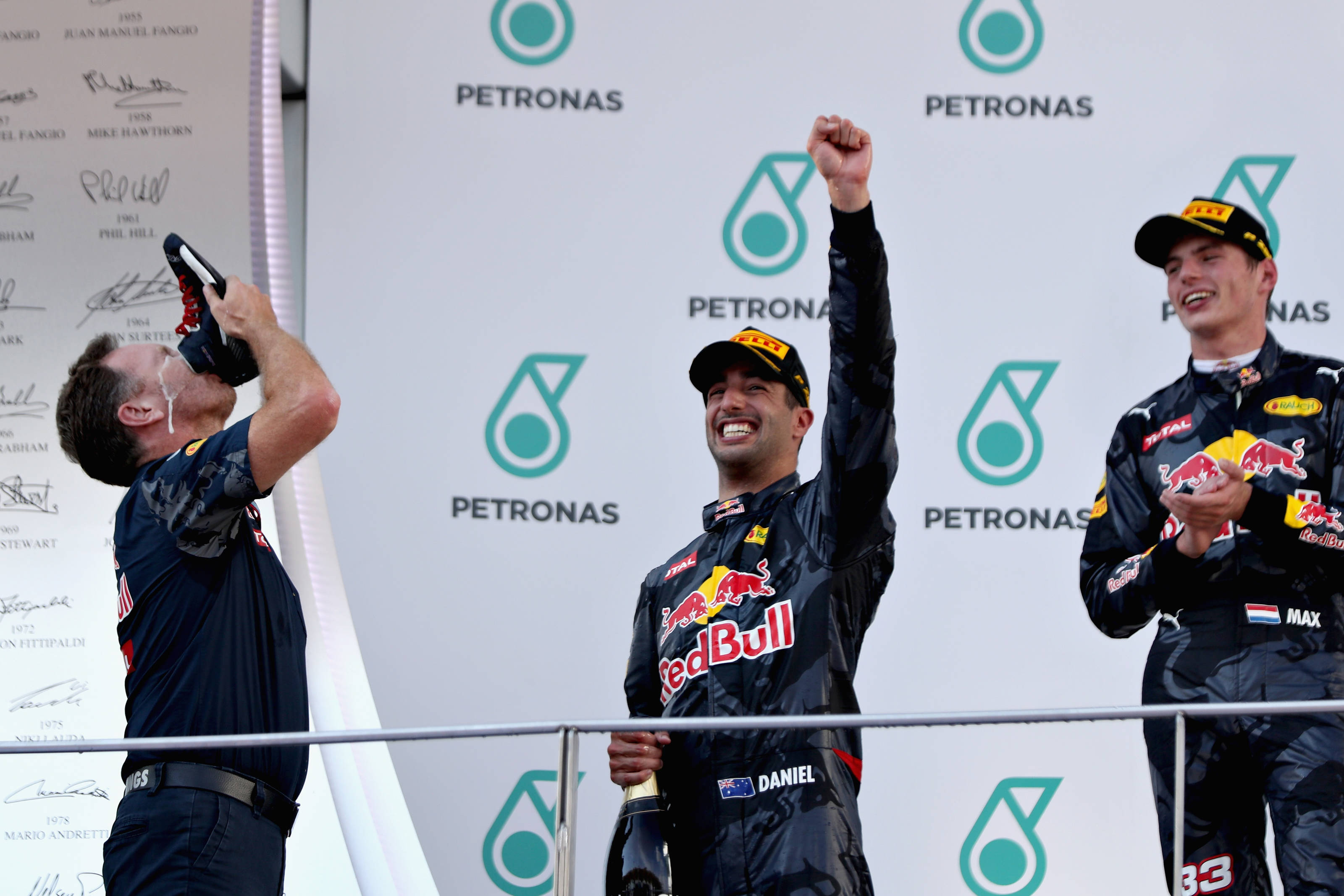 "Christian Horner, Daniel Ricciardo and Max Verstappen from Red Bull Racing share a ""shoey"" on the podium at the 2016 Malaysia GP"